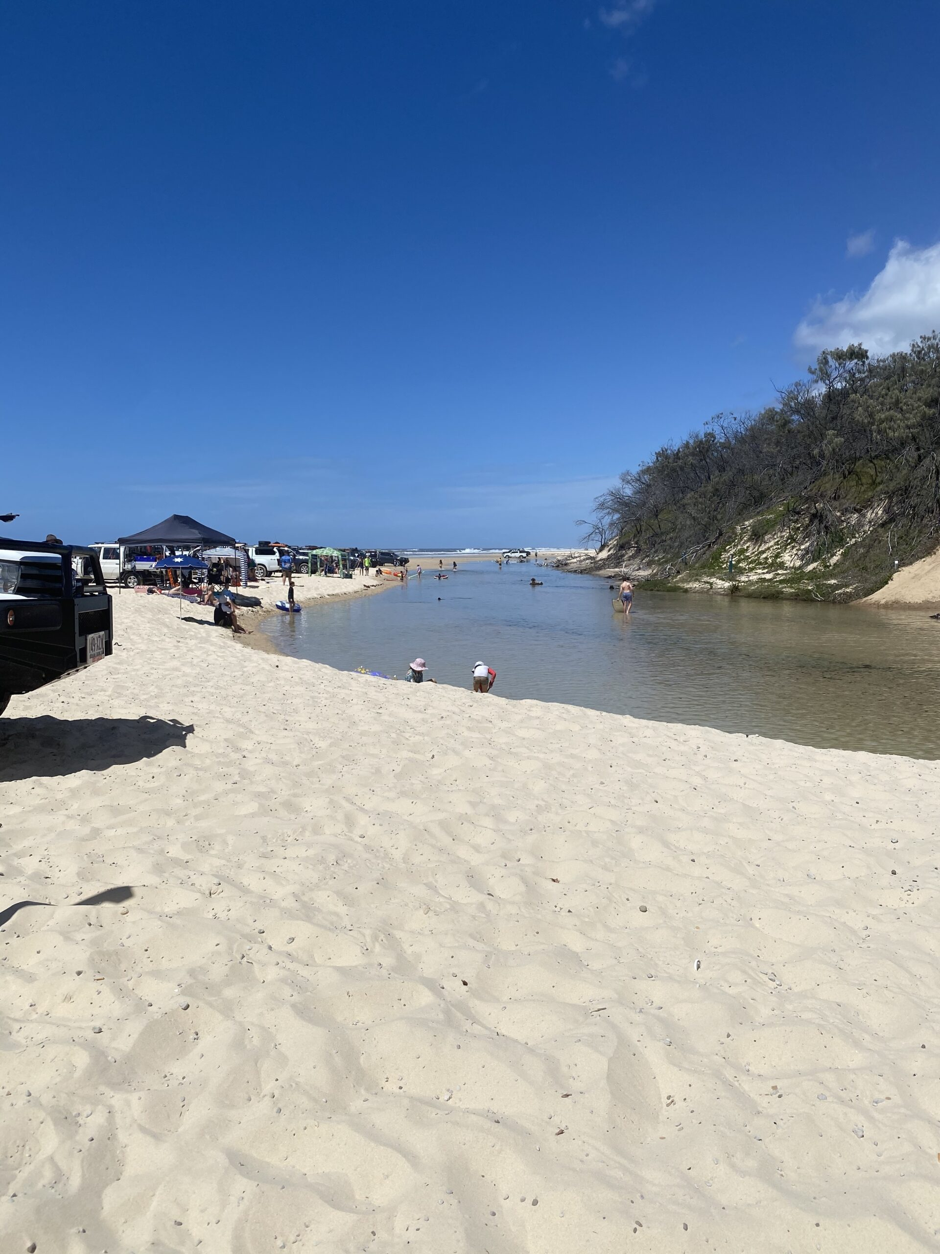 Cars parked along Eli Creek as it runs into the Ocean